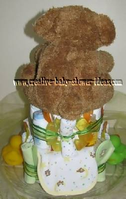 back of green and yellow teddy bear diaper cake