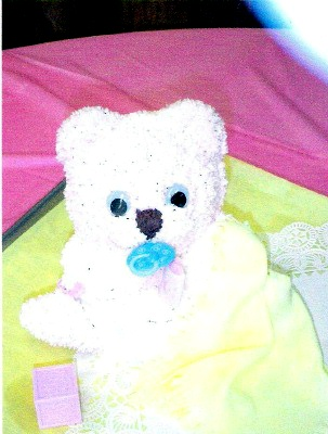 closeup of larger teddy bear cake with pacifier